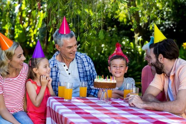 Famiglia che esamina il ragazzo di compleanno durante la celebrazione