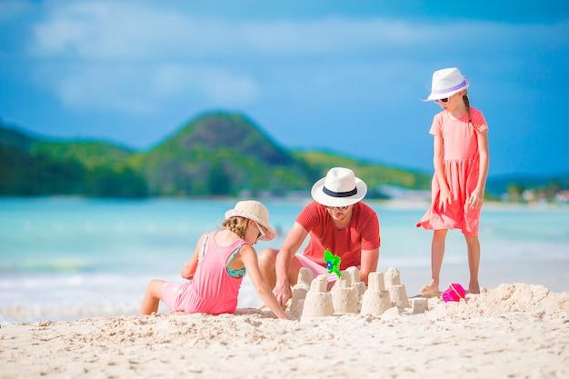 Famiglia che fa il castello della sabbia alla spiaggia bianca tropicale