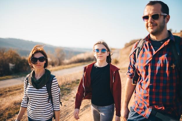 Famiglia che fa un'escursione insieme su una strada sporca della montagna