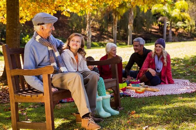 Famiglia che fa un picnic e il nonno che ride con sua nipote su una panchina