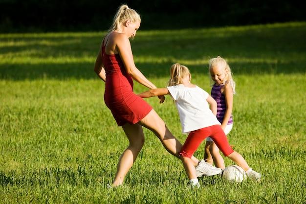 Famiglia che gioca a calcio in un campo di erba