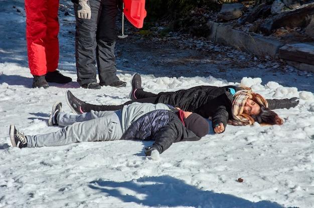 Famiglia che gioca allegramente nella neve fredda, indossando speciali indumenti termici presso la stazione sciistica