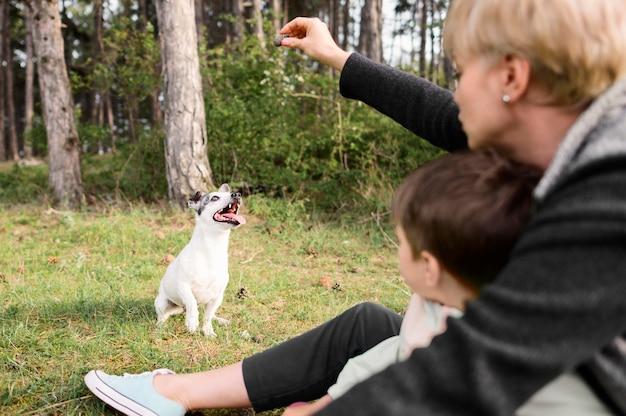 Famiglia che gioca con adorabile cagnolino