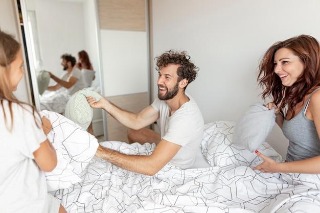 Famiglia che gioca con i cuscini nel letto
