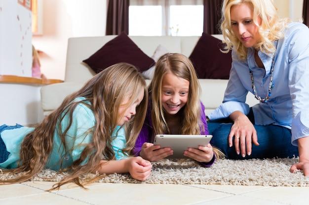 Famiglia che gioca con il computer della compressa a casa