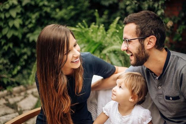 Famiglia che gode con la loro figlia nel giardino. bambina bionda graziosa nel giardino che si siede fra i suoi giovani genitori. amore e concetto di famiglia.