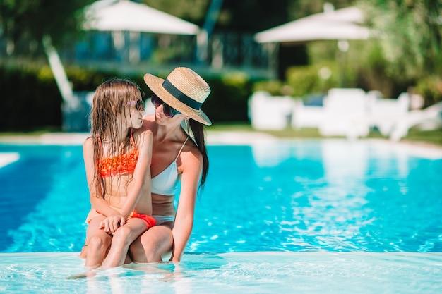Famiglia che gode delle vacanze estive nella piscina di lusso