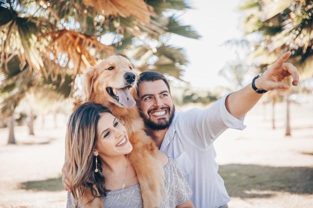 Famiglia che gode di una giornata di sole nel parco con il loro animale domestico.