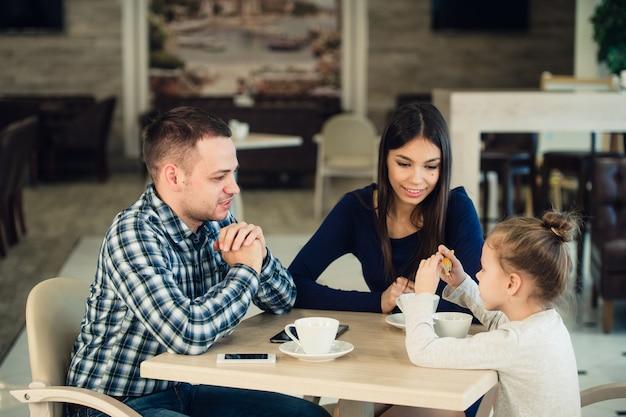 Famiglia che gode insieme del tè in caffè