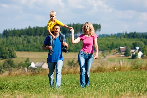 Famiglia che ha camminata sul prato