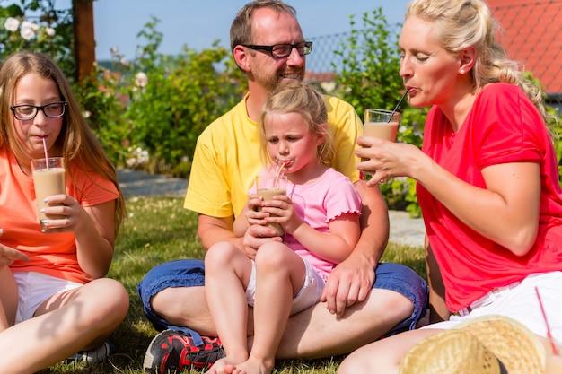 Famiglia che ha picnic nella parte anteriore del giardino della loro casa