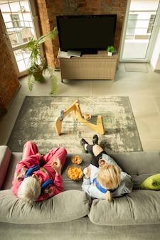 Famiglia che incoraggia e guarda la tv a casa in salotto