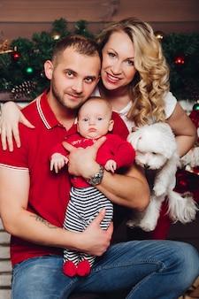 Famiglia che posa insieme vicino al camino che tiene sulle mani piccolo figlio e cucciolo bianco