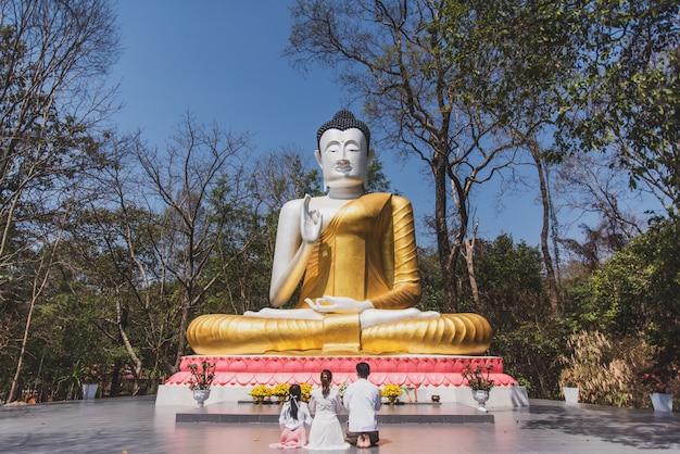 Famiglia che prega alla statua del buddha