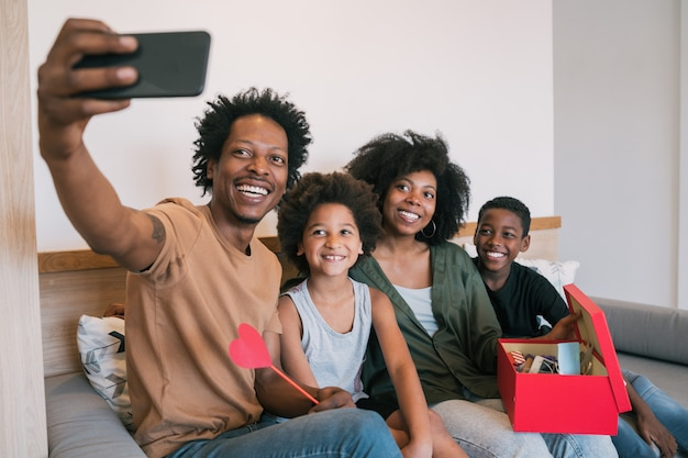Famiglia che prende selfie con il telefono mentre celebra la festa della mamma.