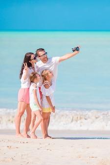 Famiglia che prende una foto del selfie sulla spiaggia. vacanza al mare in famiglia