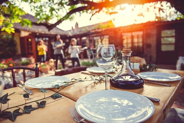 Famiglia che prepara tavolo da pranzo al patio del cortile