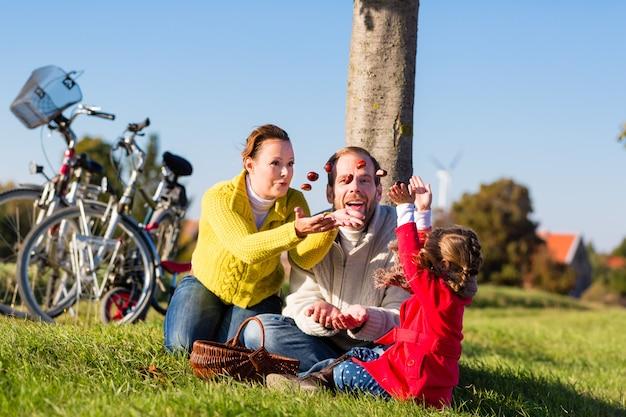 Famiglia che raccoglie castagne in gita in bicicletta