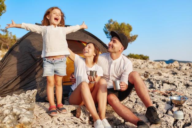 Famiglia che riposa vicino alla tenda, bambina in piedi e alzando le mani.