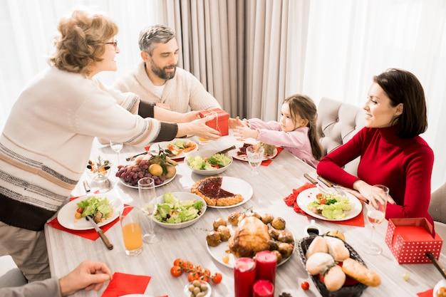 Famiglia che scambia regali sul tavolo