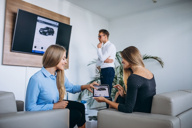 Famiglia che sceglie un'automobile in una sala d'esposizione dell'automobile