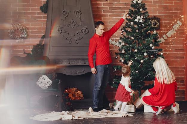 Famiglia che si siede a casa vicino all'albero di natale