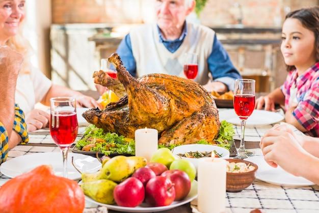 Famiglia che si siede alla tavola con prosciutto di appoggio