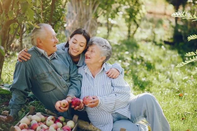 Famiglia che si siede in un giardino con le mele