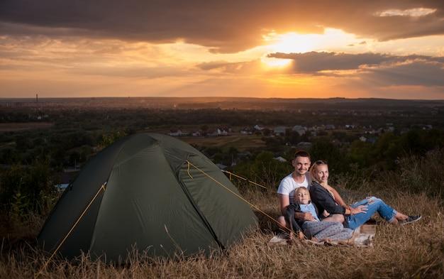 Famiglia che si siede vicino alla tenda del campo sulla collina