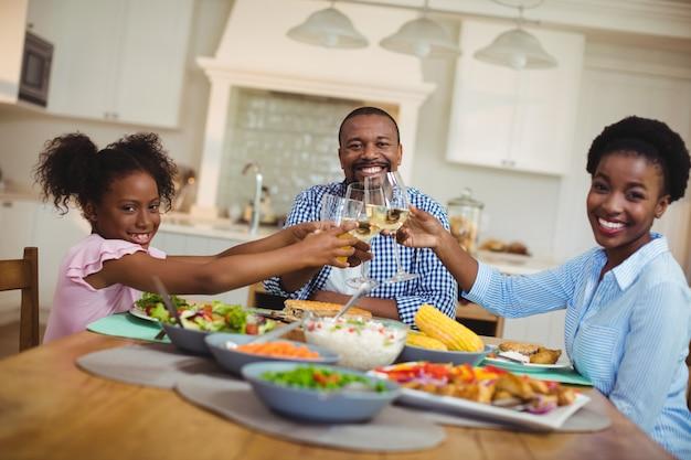 Famiglia che tosta i bicchieri di vino e del succo sul tavolo da pranzo