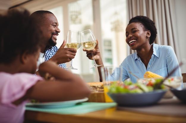 Famiglia che tosta i bicchieri di vino mentre mangiando sul tavolo da pranzo