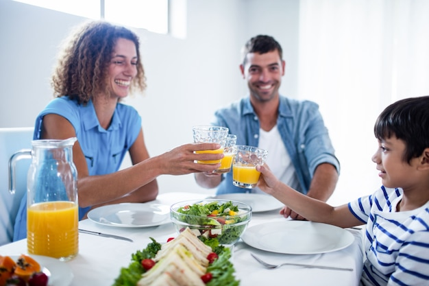 Famiglia che tosta i vetri di succo d'arancia mentre facendo colazione