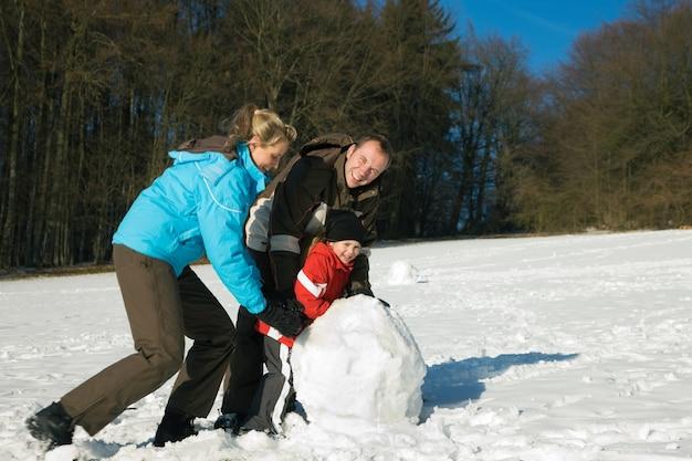 Famiglia con bambini che costruiscono pupazzo di neve
