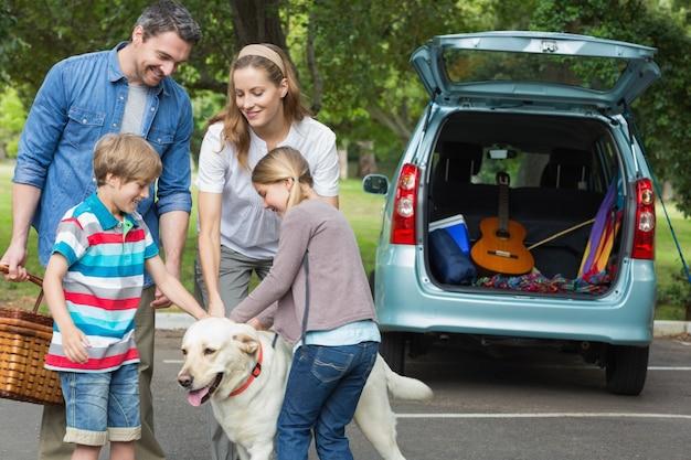 Famiglia con bambini e cane al picnic