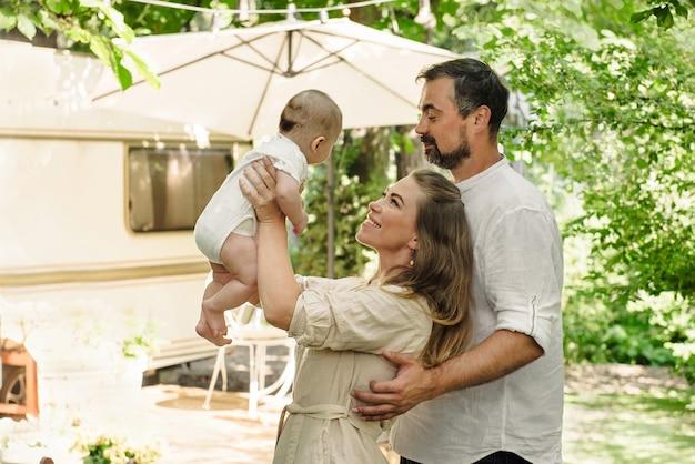 Famiglia con bambino che trascorre del tempo felice insieme vicino al rimorchio all'esterno, stile di vita in viaggio con il camper