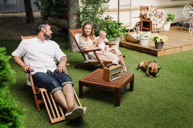Famiglia con bambino e cane che trascorrono del tempo felice insieme vicino al rimorchio fuori sulla sedia a sdraio, stile di vita itinerante con camper