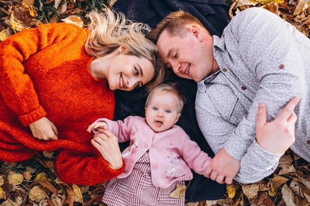 Famiglia con daugher bambino sdraiato sulle foglie nel parco