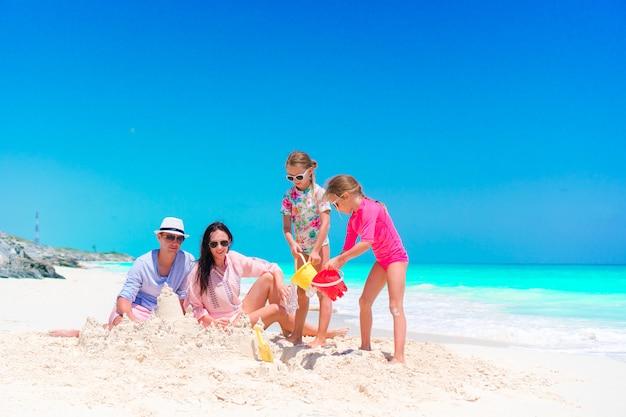 Famiglia con due bambini che fanno il castello di sabbia alla spiaggia tropicale