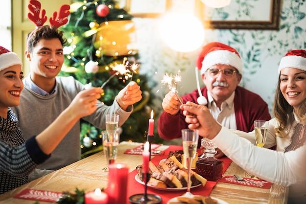 Famiglia con fuochi di bengala accesi al tavolo festivo