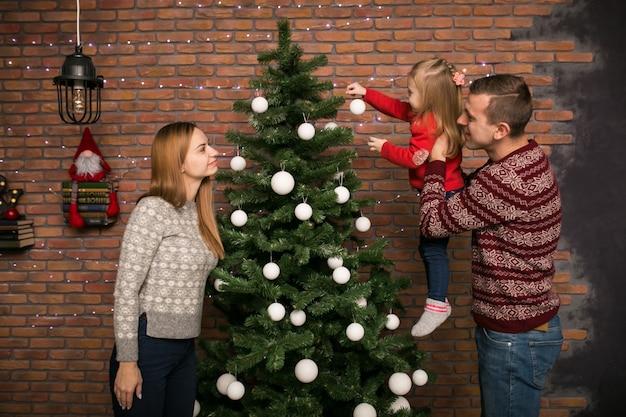Famiglia con i giocattoli d'attaccatura della piccola figlia su un albero di natale