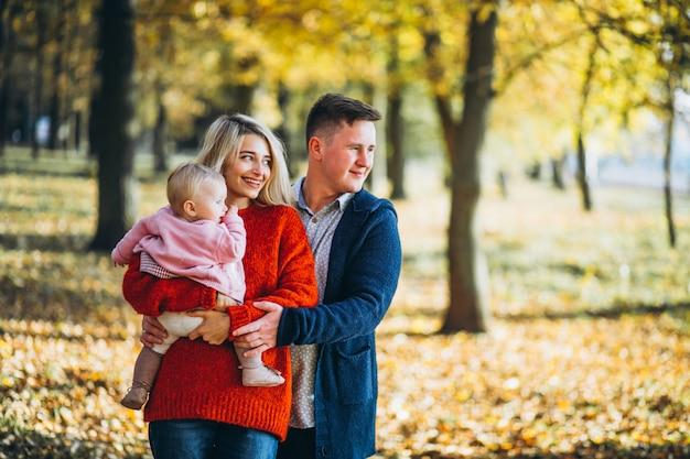 Famiglia con il bambino daugher in un parco di autunno