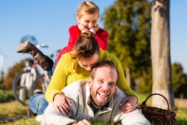 Famiglia con la bicicletta nel parco in autunno