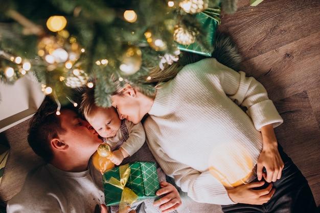 Famiglia con la figlia del bambino sotto l'albero di natale