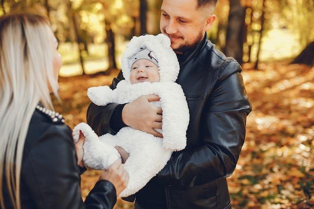 Famiglia con la figlia in un parco in autunno