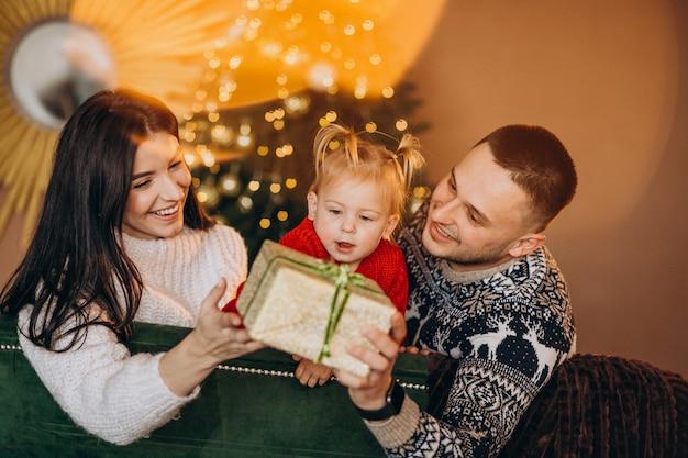 Famiglia con la piccola figlia che si siede dall'albero di natale e che disimballa il contenitore di regalo
