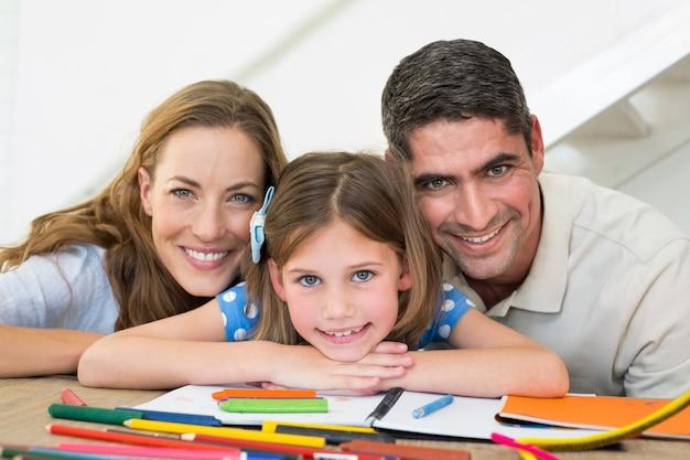 Famiglia con libro e pastelli seduto al tavolo