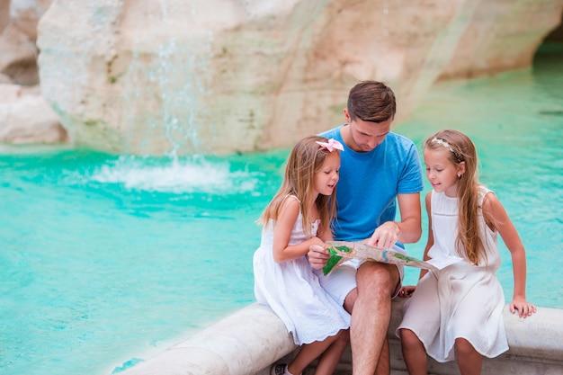 Famiglia con mappa turistica vicino a fontana di trevi, roma, italia.