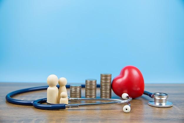 Famiglia con monete impilate in una forma del grafico e cuore con lo stetoscopio. concede un esame fisico per l'assistenza sanitaria e l'assicurazione medica.