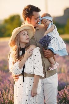 Famiglia con piccola figlia sul campo di lavanda. bella donna e bambino sveglio che giocano nel campo del prato. vacanze in famiglia in una giornata estiva.