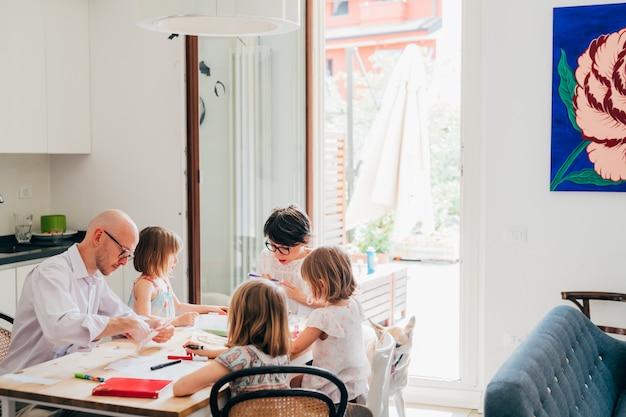 Famiglia con tre figli a casa a scuola al coperto
